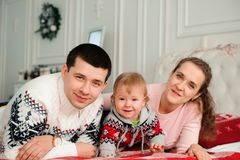 Happy smiling family with one year son near the Christmas background. stock photo