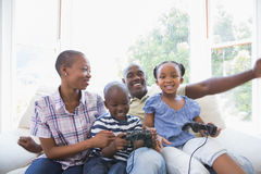 Happy smiling family playing video games together. In the living room royalty free stock image