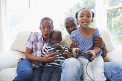 Happy smiling family playing video games together. In the living room stock photos