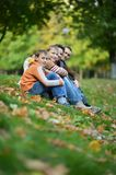 Happy smiling family sitting on leaves Stock Photos