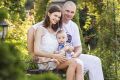 Happy smiling family of slim fit beautiful brunette mother, bold. Fat father and cute little infant baby in a green park in blue and white outfit: t-shirt stock photography