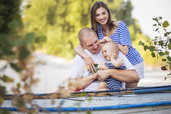 Happy smiling family of slim fit beautiful brunette mother, bold. Fat father and cute little infant baby on a seashore near nature in blue, white and red outfit stock photography