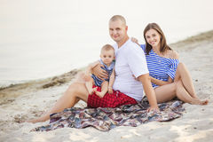 Happy smiling family of slim fit beautiful brunette mother, bold. Fat father and cute little infant baby on a seashore near water in blue, white and red outfit royalty free stock photo
