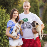 Happy smiling family of slim fit beautiful brunette mother, bold. Fat father and two cute little dogs in a green park in blue, red and white outfit: t-shirt and stock photos