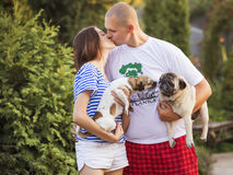 Happy smiling family of slim fit beautiful brunette mother, bold. Fat father and two cute little dogs in a green park in blue, red and white outfit: t-shirt and stock image