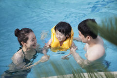 Happy smiling family teaching son how to swim in the pool Royalty Free Stock Images