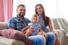 Happy smiling family of three sitting on sofa stock photography