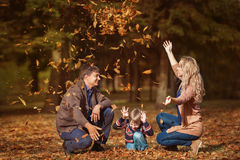 Happy smiling family throw up a leaves in a park in the autumn. Happy smiling family throw up a leaves in a park in autumn stock image