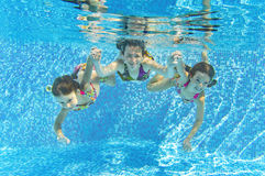 Happy smiling family underwater in swimming pool. Mother and children swim underwater in pool and having fun. Kids sport on family summer vacation. Active Stock Photography