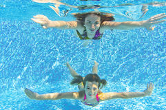 Happy smiling family underwater in swimming pool. Mother and child swim underwater in pool and having fun. Kids sport on family summer vacation. Active healthy Stock Photos
