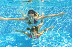 Happy smiling family underwater in swimming pool. Mother and child swim and having fun in water. Kids sport and fitness on family summer vacation. Active healthy Royalty Free Stock Images