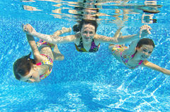 Happy smiling family underwater in swimming pool. Mother and children swim in pool and having fun. Kids sport on family summer vacation. Active healthy holiday Royalty Free Stock Images