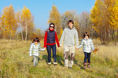 Happy smiling family walking in autumn park Royalty Free Stock Image