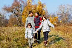 Happy smiling family walking in autumn park Stock Photo
