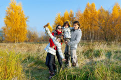 Happy smiling family walking in autumn park Stock Photos