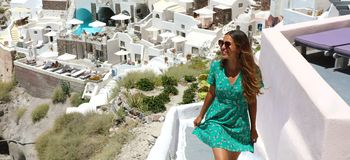 Happy smiling fashion girl with sunglasses and green dress walking in Oia village, Santorini. Excited female travel tourist on he. R summer vacations in Greece stock photography