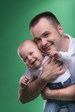 Happy smiling father embracing his baby boy. Closeup Portrait of happy smiling handsome father and cute son baby boy in white shirt and jeans posing, family Stock Photos