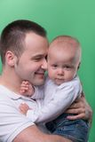 Happy smiling father embracing his baby boy. Closeup Portrait of happy smiling handsome father hugging and kissing his son baby boy in white polo shirt and jeans stock image