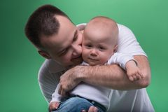 Happy smiling father embracing his baby boy. Closeup Portrait of happy smiling handsome father hugging and kissing his son baby boy in white polo shirt and jeans Royalty Free Stock Images