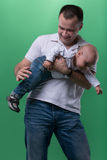 Happy smiling father embracing his baby boy. Half-length portrait of happy smiling handsome father clapping his son baby boy bottom, funny family concept royalty free stock image