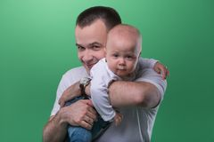 Happy smiling father embracing his baby boy. Half-length portrait of happy smiling handsome father embracing his baby boy, family concept, isolated on green royalty free stock images