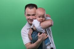 Happy smiling father embracing his baby boy. Half-length portrait of happy smiling handsome father embracing his baby boy, family concept, isolated on green stock photo