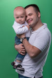 Happy smiling father embracing his baby boy. Half-length portrait of happy smiling handsome father embracing his baby boy, family concept, isolated on green stock image