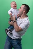 Happy smiling father embracing his baby boy. Half-length portrait of happy smiling handsome father and his son baby boy playing around and laughing, family royalty free stock images