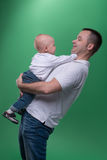 Happy smiling father embracing his baby boy. Half-length portrait of happy smiling handsome father and his son baby boy playing around and laughing, family Royalty Free Stock Image