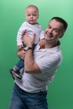 Happy smiling father embracing his baby boy. Half-length portrait of happy smiling handsome father and his son baby boy posing and smiling at camera, family Royalty Free Stock Photos