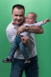 Happy smiling father embracing his baby boy. Half-length portrait of happy smiling handsome father embracing his son baby boy, baby is stretching his arms royalty free stock photos