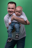 Happy smiling father embracing his baby boy. Portrait of happy smiling handsome father and his son baby boy in white polo shirt and jeans posing, family concept stock images