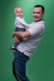 Happy smiling father embracing his baby boy. Portrait of happy smiling handsome father and his son baby boy in white polo shirt posing and smiling, family royalty free stock image
