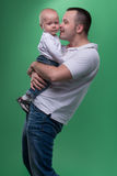 Happy smiling father embracing his baby boy. Portrait of happy smiling handsome father and his son baby boy in white polo shirt posing and smiling, family stock image