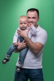 Happy smiling father embracing his baby boy. Waistup Portrait of happy smiling handsome father and cute son baby boy in white shirt and jeans looking forward at Royalty Free Stock Photo