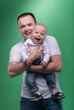 Happy smiling father embracing his baby boy. Waistup portrait of happy smiling handsome father and cute son baby boy in white shirt and jeans posing, family Stock Photo
