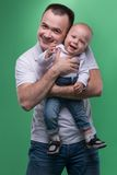 Happy smiling father embracing his baby boy. Waistup portrait of happy smiling handsome father and cute son baby boy in white shirt and jeans posing, family Stock Photos