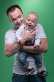 Happy smiling father embracing his baby boy. Waistup portrait of happy smiling handsome father and cute son baby boy in white shirt and jeans posing, family Royalty Free Stock Photos