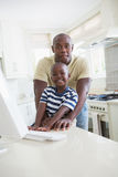 Happy smiling father with his son using computer Stock Photo