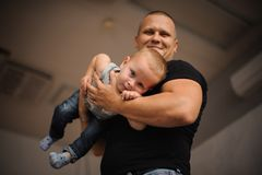 Happy smiling father holding a son in his hands. Happy smiling father holding a cute little son in his hands on the blurred background Stock Photos
