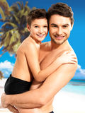 Happy smiling father hugs son at tropical beach. Portrait of happy smiling father hugs son 8 years old at tropical beach stock photography