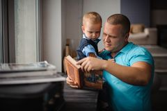 Happy smiling father and little son reading book. Portrait of happy smiling father and his little son reading book in flat near the window royalty free stock photos