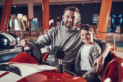 Happy smiling father and son sitting on toy car royalty free stock photos