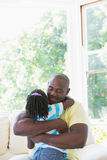 Happy smiling father to hug with her daughter in couch Royalty Free Stock Photos