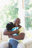 Happy smiling father to hug with her daughter in couch Stock Images