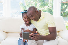 Happy smiling father using digital tablet with her daughter on couch Stock Photography