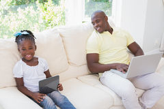 Happy smiling father using laptop and her daughter using tablet on couch Stock Photo