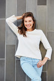 Happy smiling female fashion model posing against a wall Royalty Free Stock Photos