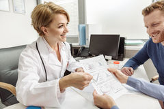 Happy smiling female medico working. Cheerful doctor is sitting near table. She looking at patients and paying attention to sheet of paper with diagrams Royalty Free Stock Images
