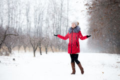 Happy smiling female in red winter jacket enjoys the snow, outdo Royalty Free Stock Images